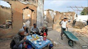 Ethnic Uzbeks eat outside their destroyed house on 7 October 2010