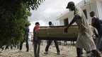 People carry a coffin out of the St Nicholas hospital in Saint-Marc (21 October 2010)