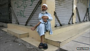 Shopkeeper Muhammad Hussain sits outside a closed market in Karachi on 17 September 2010