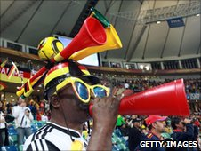 A South African fan wearing and blowing vuvuzelas