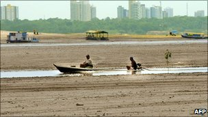 Two fishermen on a boat on the dried bed of the Negro river, 120km from Manaus