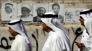 Bahraini men walk past election posters in the village of Diraz (22 October 2010)