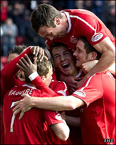 Chris Maguire is mobbed by Dons team-mates after scoring the opener