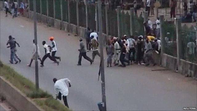 Protesters break through a fence