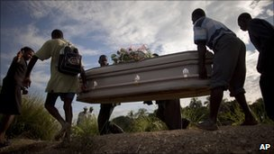 People carry a coffin containing the remains of a relative who died of cholera in Robine, Haiti (23 October 2010)