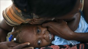 Child with cholera is comforted by a woman in hospital in Grand-Saline, Haiti, 23 October 2010