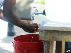 Health worker washing her hands outside St Nicholas hospital, St Marc, Haiti (24 Oct 2010)