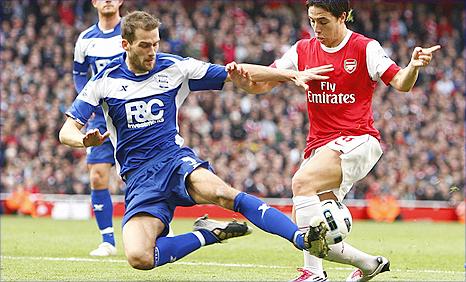 Birmingham City centre-back Roger Johnson (left) tackling Arsenal midfielder Samir Nasri
