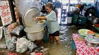 A woman cooks food as her restaurant is inundated with floodwater after heavy rains in the Thai capital Bangkok