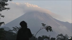 A man watches Mount Merapi as seen from Kaligendol, Yogyakarta, Indonesia, Wednesday, Oct. 27, 2010