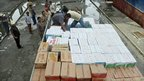 Men load some 16-tonnes of aid from the Disaster Management Agency and several ministries for earthquake and tsunami victims in the Mentawai islands, at the port in Padang in West Sumatra on 27 October 2010