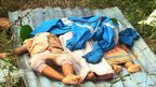 Bodies lie in the tsunami-hit Muntei Baru Baru village, in the Cikakap sub-district of Indonesia&#039;s Mentawai islands 26 October 2010. 