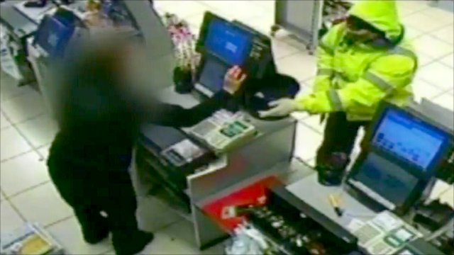 CCTV image of masked robbery with axe