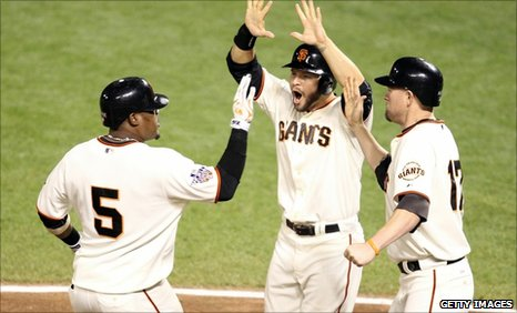 Juan Uribe (left) celebrates his home run with Cody Ross and Aubrey Huff
