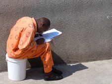 Man sitting on bucket in prison overalls in Leeuwkop Prison