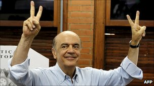 Jose Serra makes the victory sign after casting his vote in Sao Paulo