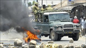 Riot police drive past burning tyre in Dar es Salaam