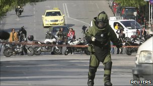 A police explosives expert arrives to detonate a suspicious package (1 Nov 2010)