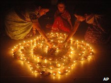 Women lighting earthen lamps on the eve of the Hindu festival of Diwali. Photo: Associated Press