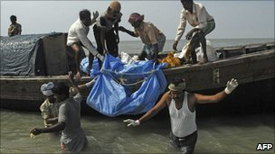 Fishermen carry a recovered body from the waters near Kakdwip, some 100km south of Calcutta, on 2 November, 2010, following the sinking of a ferry on 30 October.