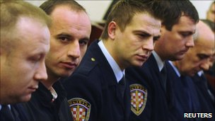 Robert Matanic (2nd L) and Slobodan Djurovic (5th L) sit between court policemen while waiting for the verdict