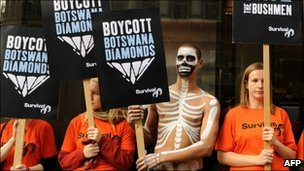 Demonstrators hold placards as they protest outside De Beers in central London