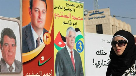 Woman walking past election campaign posters in the Jordanian capital Amman
