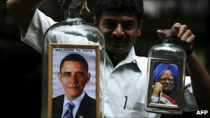 Indian artist Basavaraju S Gowda holds a bottle containing a framed portrait of President Obama and Indian PM Manmohan Singh on November 4, 2010
