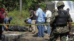 Police exhume the body of one of 18 murdered men from Michoacan from a mass grave near Acapulco
