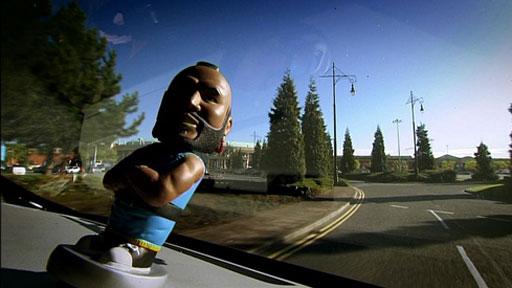 A Mr T toy sitting on a dashboard
