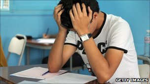 A child with his head in his hands studying an exam paper.