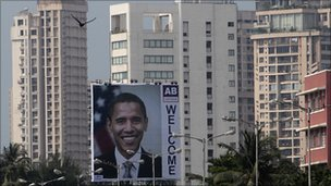 Birds fly past a billboard depicting US President Barack Obama in Mumbai