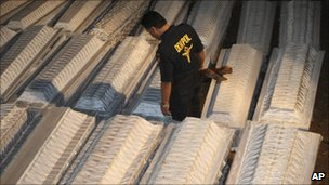 A policeman walks through coffins of earthquake victims in Yogyakarta, 7 November