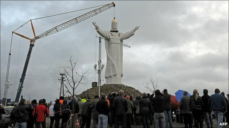 People watch as a crane lifts into place the statue's head in Swiebodzin. Photo: 6 November 2010