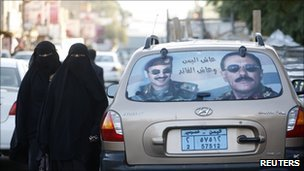 Veil-clad women walk past a car with a sticker portraying Yemeni President Ali Abdullah Saleh and his eldest son Ahmed, in Sanaa