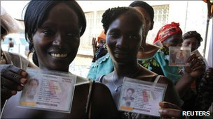 Voters show their electoral cards as they wait to vote in Conakry. Photo: 7 November 2010