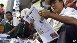 Man reads a newspaper in Rangoon, Burma, 8 November 2010