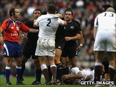 Lewis Moody holds his head on the ground as Steve Thompson squares up to Mealamu (left)