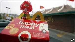 A toy sitting atop a fast-food meal outside a McDonald&#039;s restaurant
