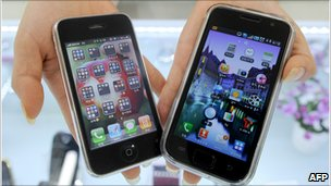 A shopkeeper in South Korea holds the Galaxy S from Samsung (right) and Apple's iPhone 3G