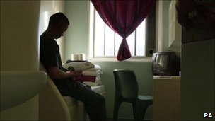 A young offender reads in his room