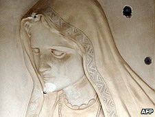 Bullet holes in a stone relief of the Virgin Mary at the Cathedral of Our Lady of Deliverance in Baghdad