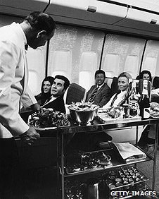 Passengers being served drinks on a flight in 1970