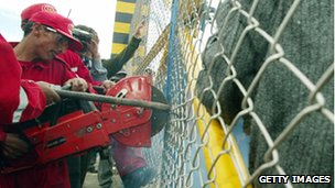 Policemen cut the fence of a Swiss-owned factory in Vinto, Bolivia, in February 2007 after President Evo Morales nationalises the company