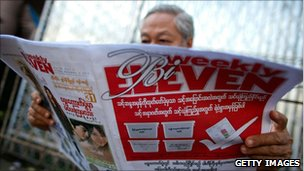 Man reads newspaper in Rangoon