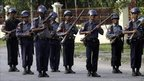 Riot police officers stand guard on a road leading to Aung San Suu Kyi's home.