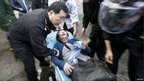Rescuers rush a survivor to an ambulance during a fire at a residential building in Shanghai, 15 November 2010