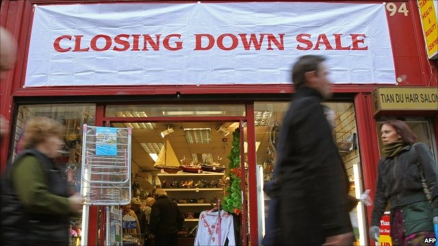 People walk past shop holding a closing down sale in Dublin