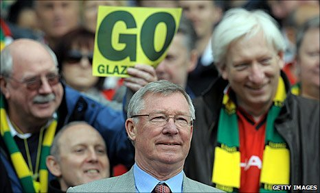 Manchester United fans protesting against the Glazers behind manager Sir Alex Ferguson