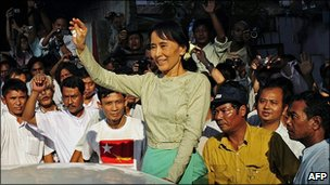 Aung San Suu Kyi (C) waves to supporters as she arrives at the National League for Democracy (NLD) headquarters in Yangon on November 15, 2010